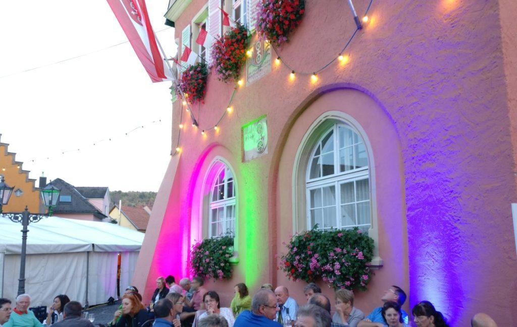 Das Rathaus ist beleuchtet. Am Fuße seiner Mauern sitzt der Rheinhesse und erfreut sich am Gespräch mit dem Tischnachbarn und dem Wein.
